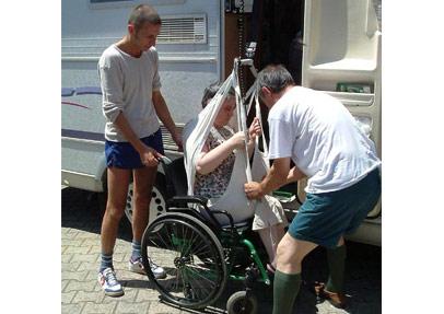 Viaggio2 - Aiutato da Fabrizio, che sfila la carrozzina, Alberto, sostiene Antonella nel sollevamento.